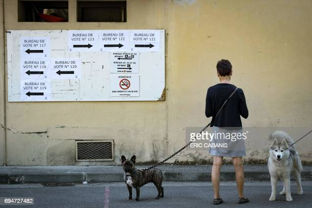 TOPSHOT A woman and two dogs stand outside a polling station in Toulouse during the first round of the French legislative elections on June 11 2017 /...