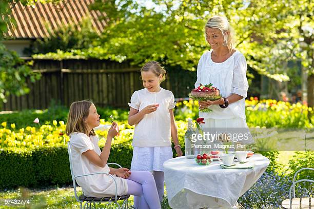 Woman and two girls with a strawberry cake in a garden, Sweden.