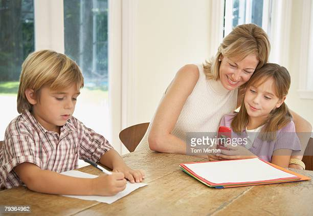 Woman and two kids with mobile phone and homework at kitchen table