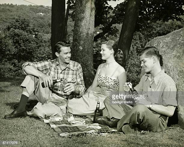 Woman and two men picnicking, (B&W)