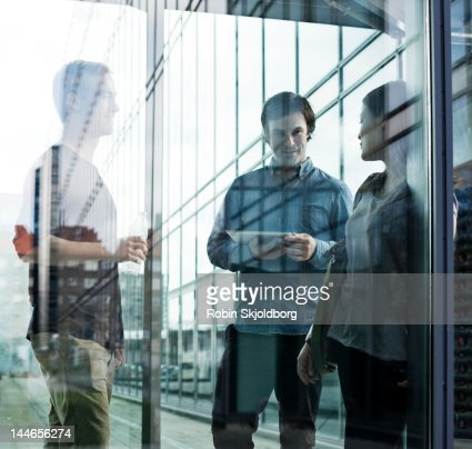Woman and two men talking behind glass. : Stock Photo