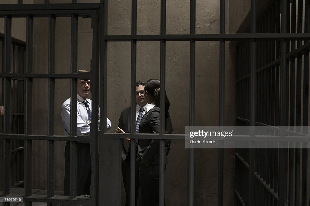 Woman and two men talking in prison cell : Stock Photo