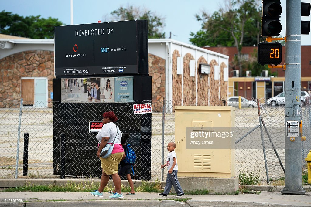 A woman and two small children negotiate Colfax Ave and Peoria next to as of yet too be developed land June 24, 2016.