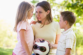 Woman and two young children outdoors holding volleyball telling off kids