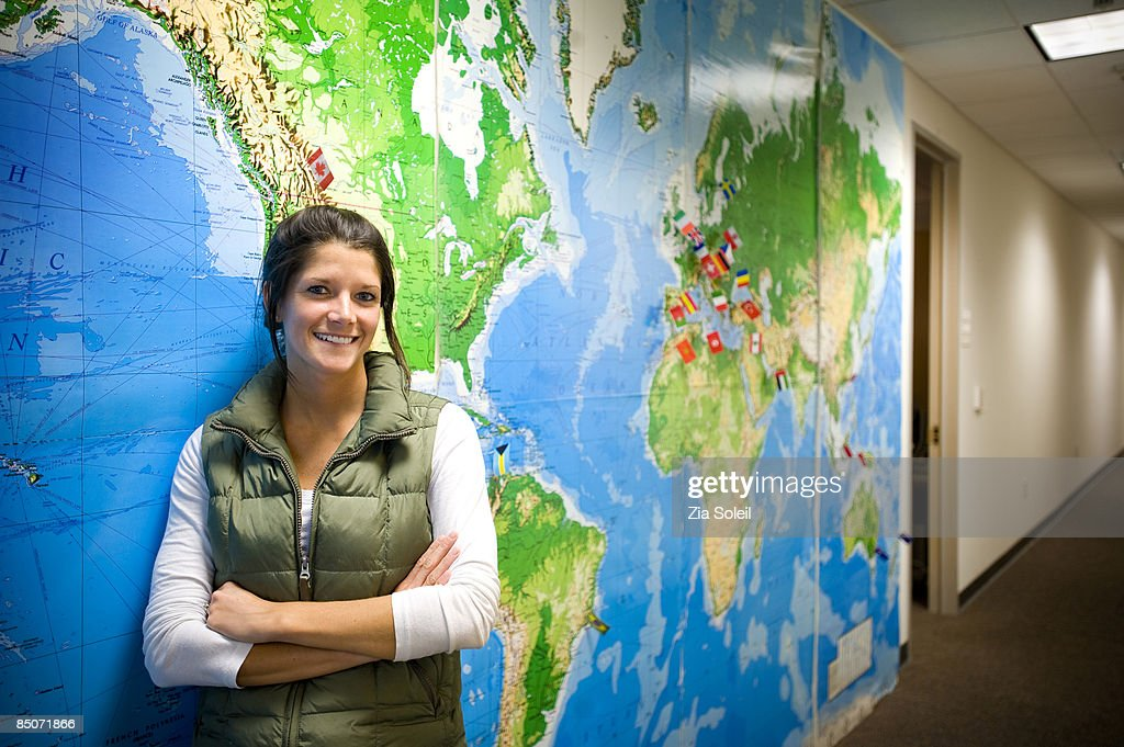 woman and world map, corporate hallway : Stock Photo