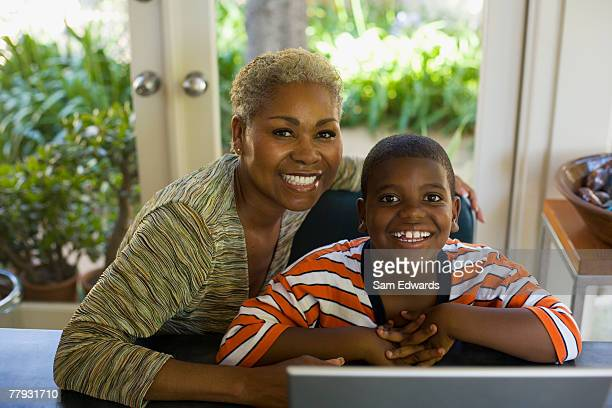 Woman and young boy at table with laptop smiling