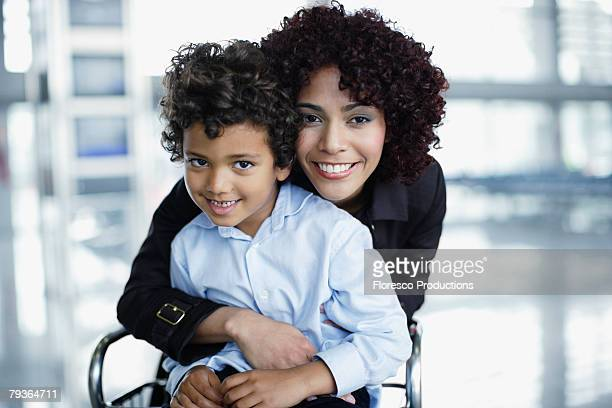 Woman and young boy in airport being affectionate