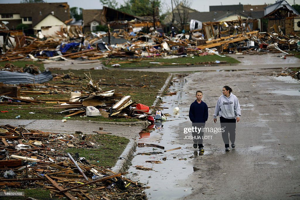 A woman and young boy walk along a street as they view destroyed house on May 21, 2013 in Moore, Oklahoma. Families returned to a blasted moonscape that had been an American suburb Tuesday after a monstrous tornado tore through the outskirts of Oklahoma City, killing at least 24 people. Nine children were among the dead and entire neighborhoods vanished, with often the foundations being the only thing left of what used to be houses and cars tossed like toys and heaped in big piles. AFP PHOTO/Joshua LOTT