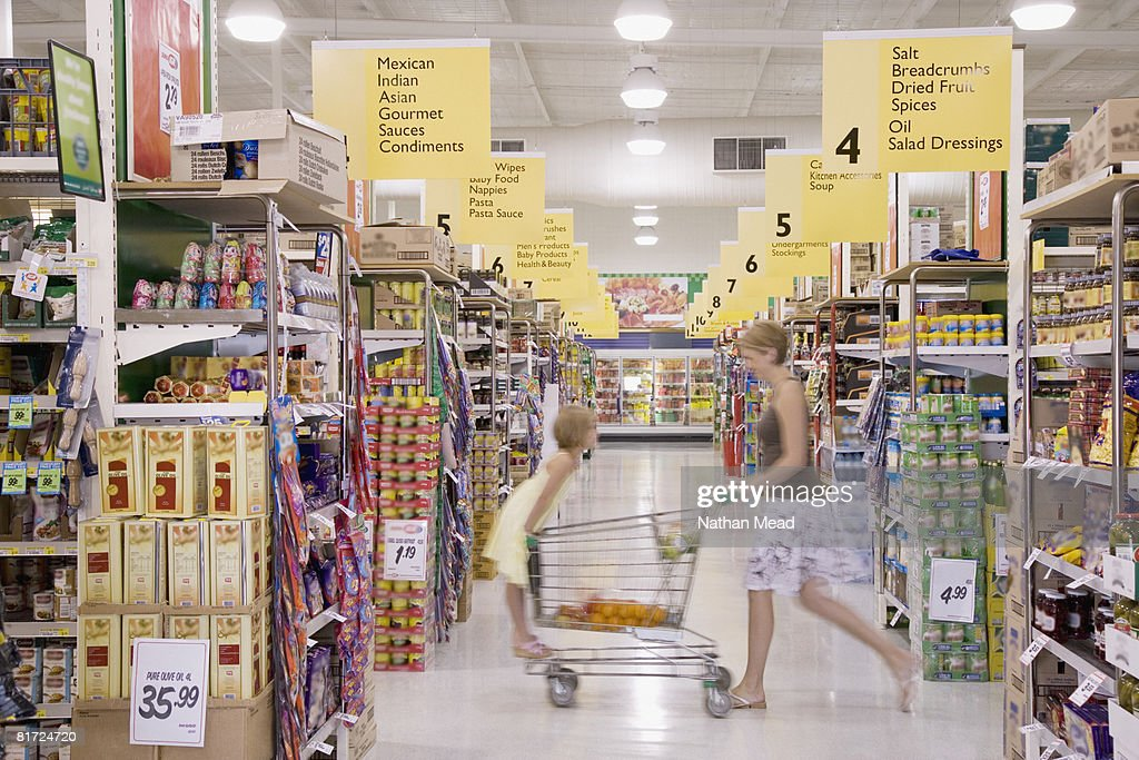 Woman and young girl in grocery store with shopping cart : Stock Photo
