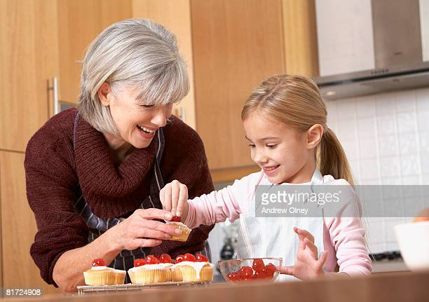Woman and young girl in kitchen putting cherries onto cupcakes and smiling