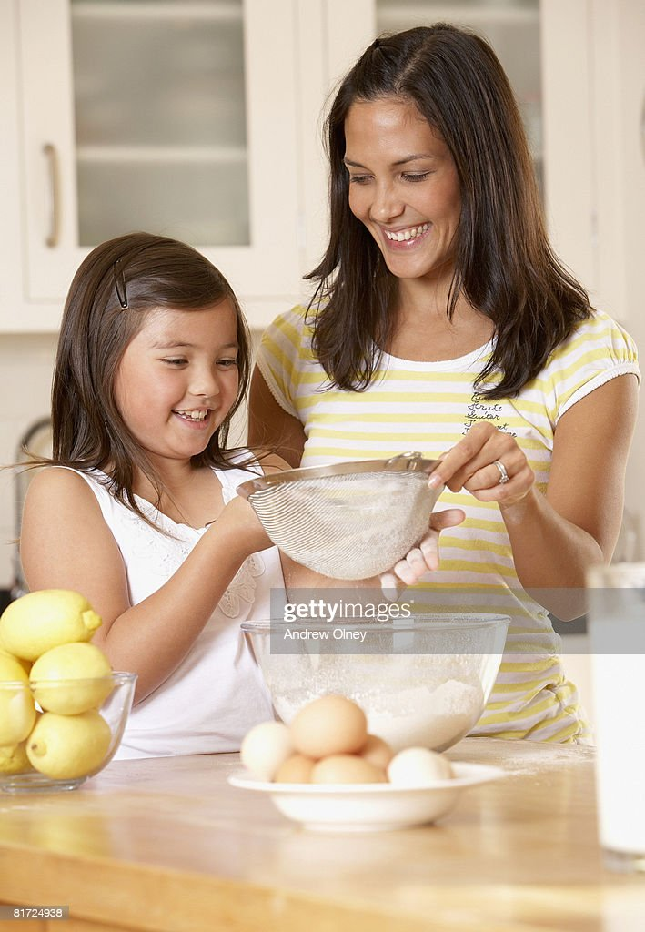 Woman and young girl in kitchen sifting flour into a bowl and smiling : Stock-Foto