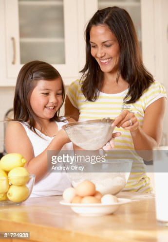 Woman and young girl in kitchen sifting flour into a bowl and smiling : Foto de stock