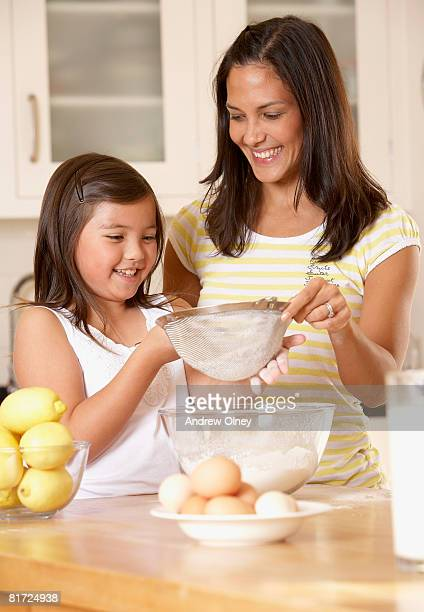 Woman and young girl in kitchen sifting flour into a bowl and smiling