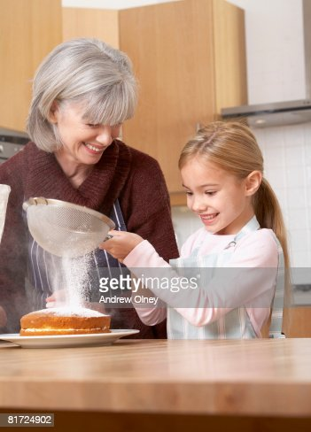 Woman and young girl in kitchen sifting icing sugar onto a cake and smiling : Stock Photo