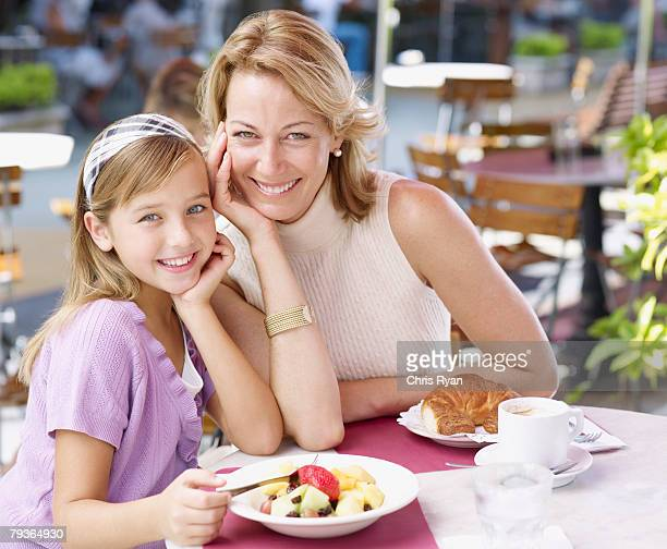 Woman and young girl on outdoor patio eating meal