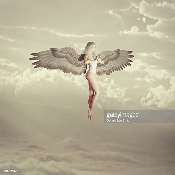 Woman angel flying in clouds