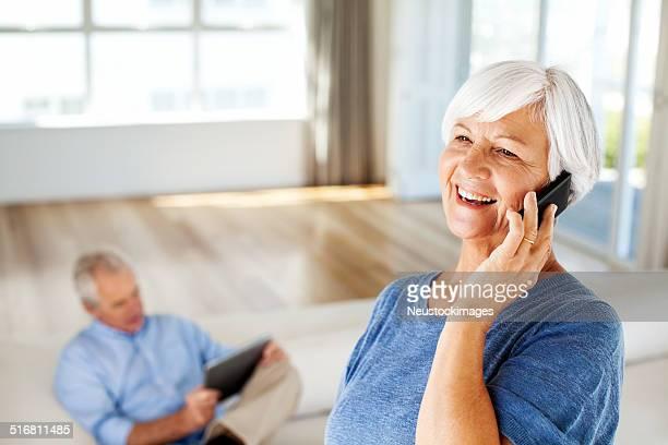 Mulher Responder a chamada no telefone inteligente em Casa