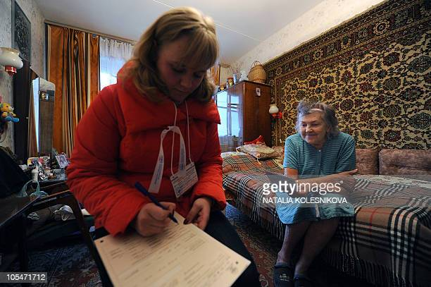 A woman answers questions of a census taker visiting her apartment in Moscow on October 14 during the first day of Russia's nationwide census From...