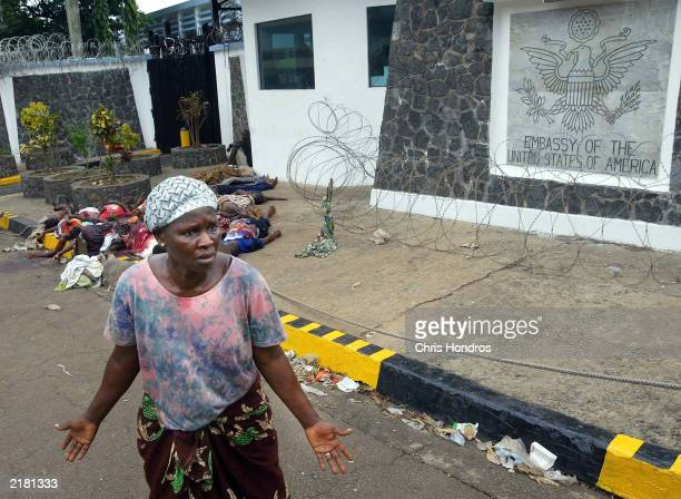 A woman appeals for international help while a pile of some 18 bodies apparently killed in rebel shelling sits in front of the US embassy July 21...