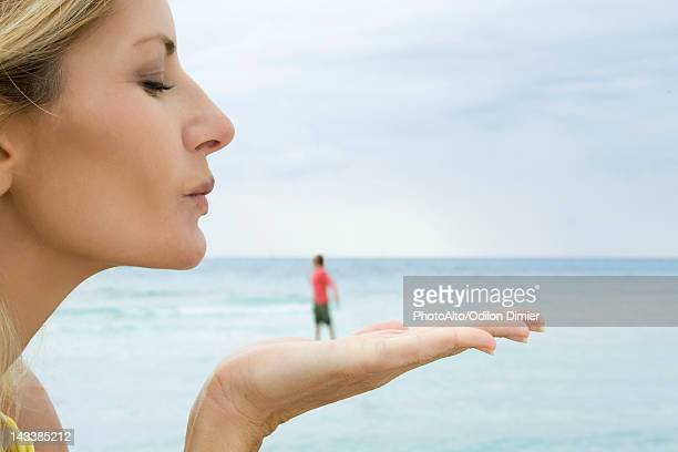 Woman appearing to blow a kiss at tiny man standing on her hand
