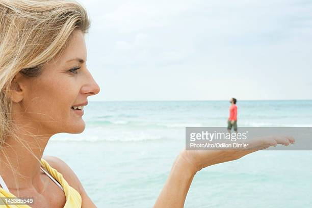 Woman appearing to hold tiny man in her hand at the beach