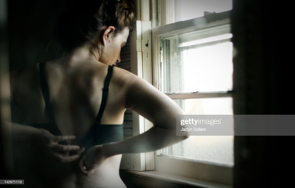 Woman appears to be putting on her bra : Stock Photo