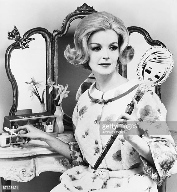 A woman applies some cosmetic cream at the dressing table 1953