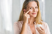 Smiling senior woman applying anti-aging lotion to remove dark circles under eyes. Happy mature woman using cosmetic cream to hide wrinkles below eyes. Lady using day moisturizer to counteract the agi