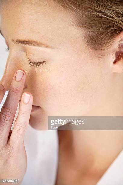Woman Applying Beauty Cream Under Eyes