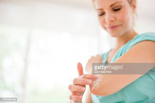 Woman applying body lotion