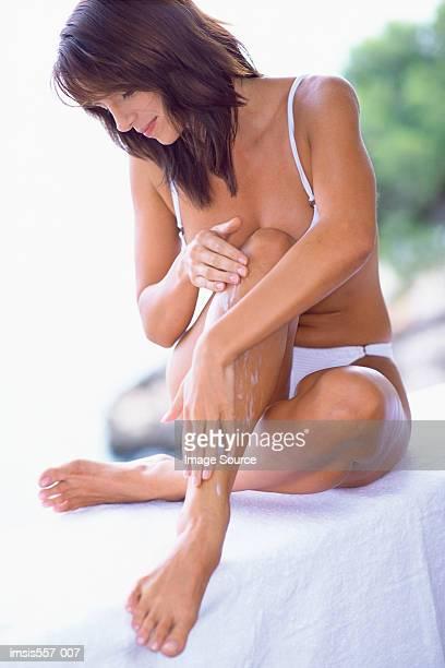 Donna applicando cosmetici crema