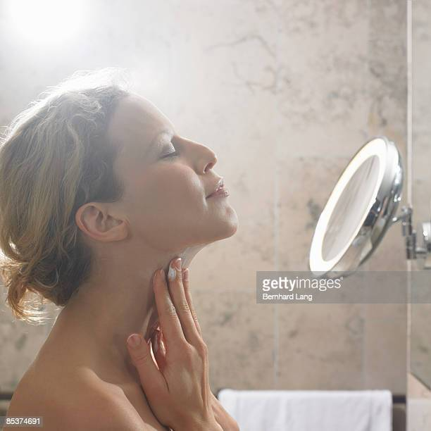 Woman (36y) applying cream on neck