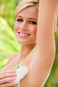 Woman applying deodorant under her arm