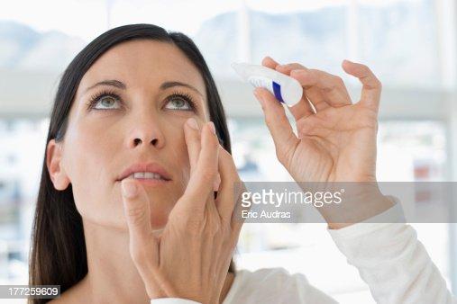 Woman applying eye drops into eye