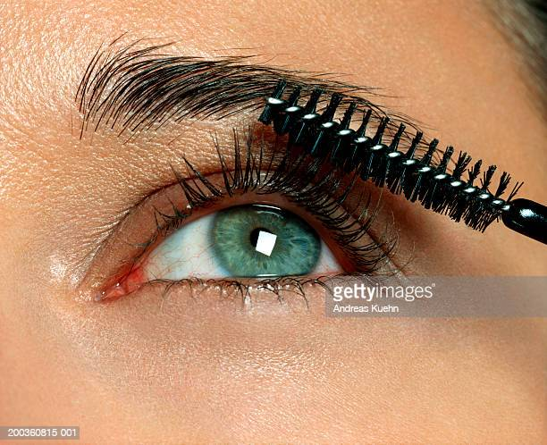 Woman applying eyelash makeup, close-up