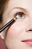 A woman applying eyeliner, detail of eye