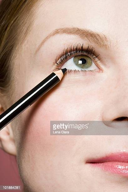 A woman applying eyeliner, detail of eye