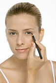 Woman applying eyeliner, smiling at camera, close-up