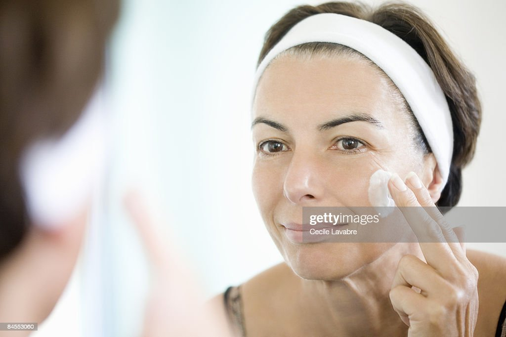 Woman applying face cream in front of mirror