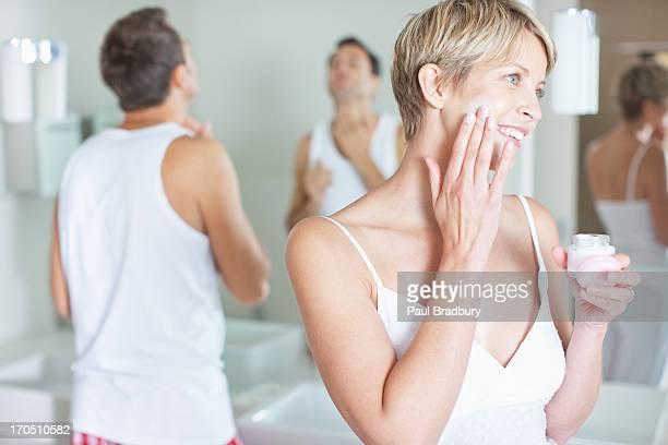 Femme appliquer la crème pour le visage dans le matin