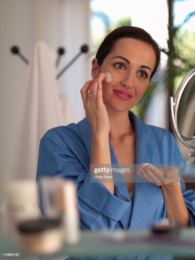 Woman applying face cream : Stock Photo