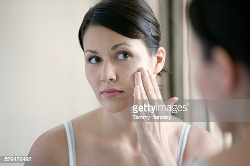 Woman applying face cream : Stock Photo