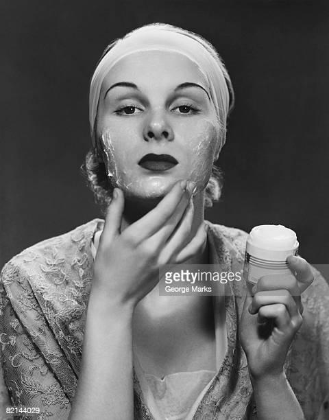 Woman applying face cream, (B&W)