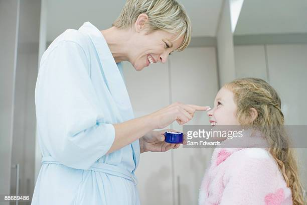 Woman applying face cream to daughters nose