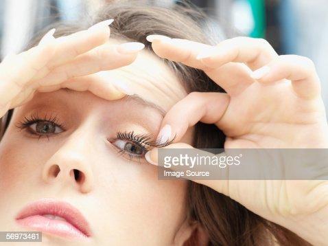 Woman applying fake eyelashes
