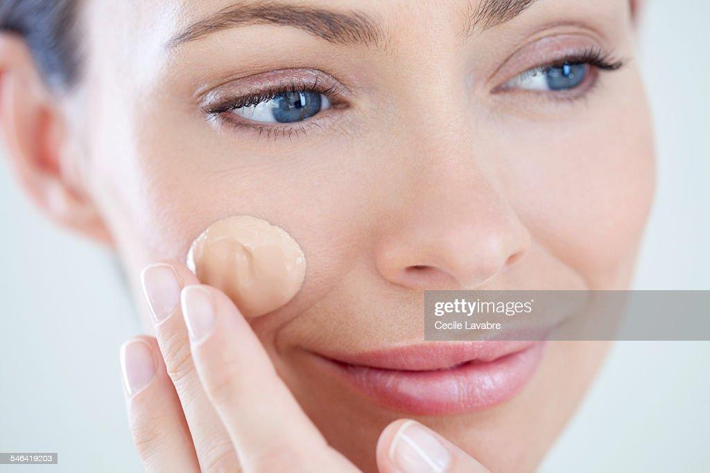 Woman applying foundation : Stock Photo