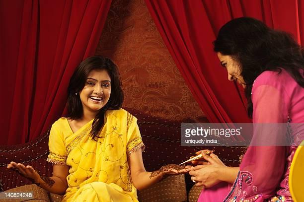 Woman applying henna on a bride's hand