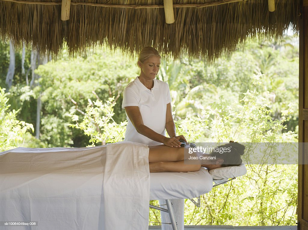 Woman applying hot stone therapy to woman lying down on massage bed : Stock Photo