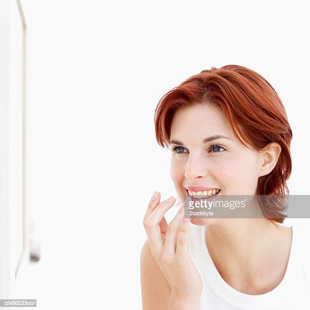 woman applying lip gloss with finger