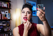 Woman applying lipgloss before going out.